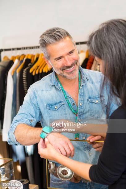 Woman holding bracelet on wrist of man
