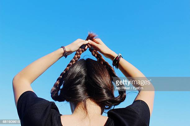 Woman Holding Braided Hair Up Against Clear Sky