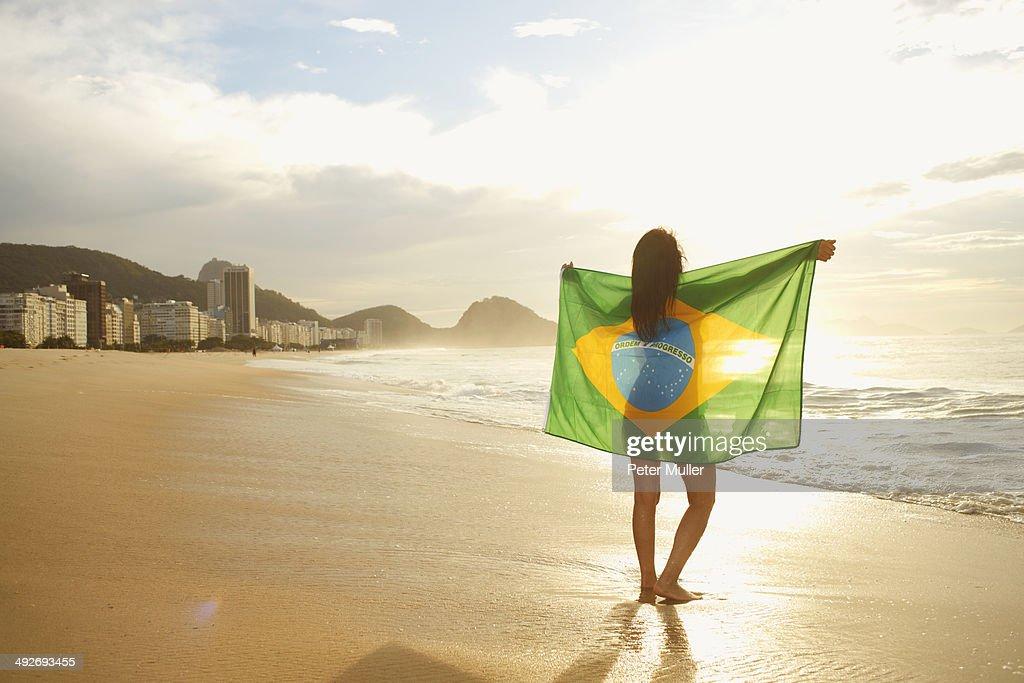 Woman holding Brazilian flag on Copacabana Beach, Rio, Brazil : Stock-Foto
