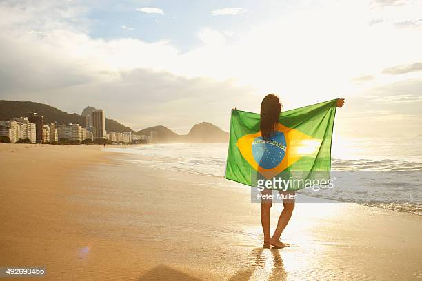 Woman holding Brazilian flag on Copacabana Beach, Rio, Brazil