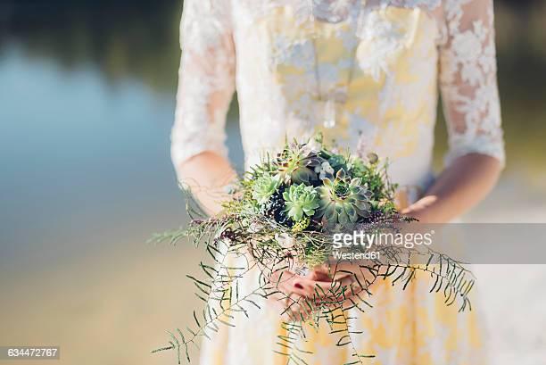 Woman holding bridal bouquet, close-up