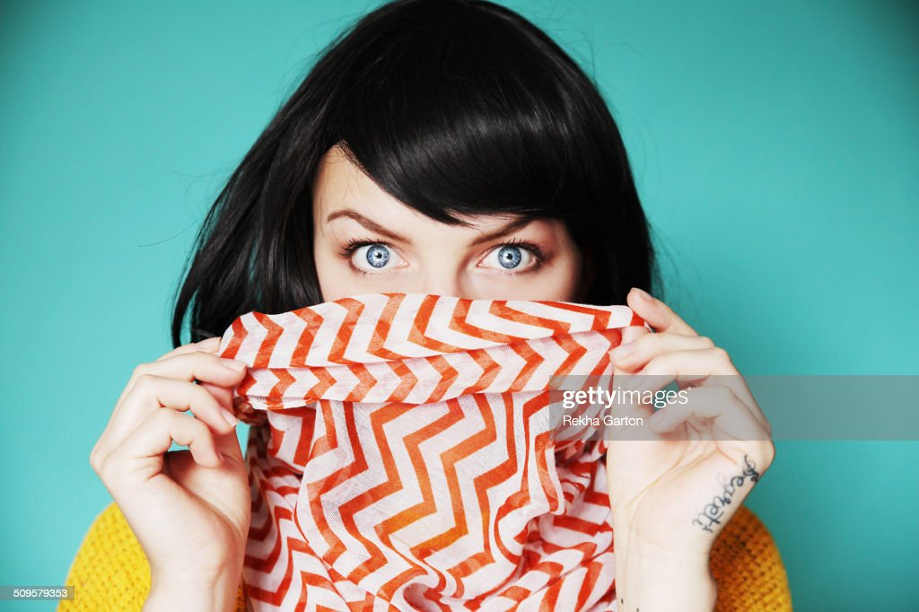 Woman holding bright scarf over lips with shock : Foto stock