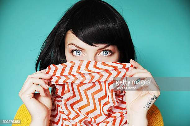 Woman holding bright scarf over lips with shock
