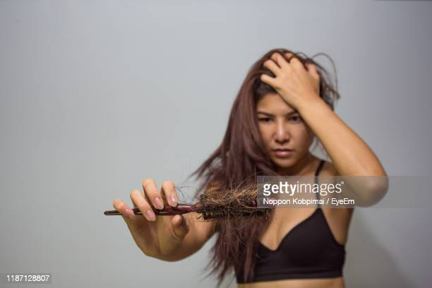 woman holding brush with hair against gray background - ヘアロス ストックフォトと画像