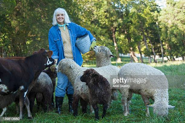 Woman holding bucket and standing with calf and sheep