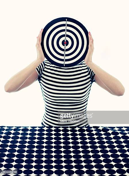 Woman Holding Bullseye in Front of Face