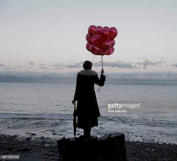 Woman holding bunch of red balloons standing large driftwood tree stump on beach