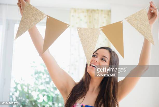 woman holding bunting flags in living room - party decoration stock pictures, royalty-free photos & images