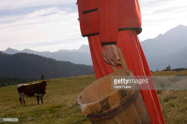 'Woman holding butter tub, cow in background'
