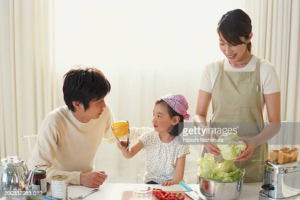 Woman holding cabbage and man looking at daughter (3-5)