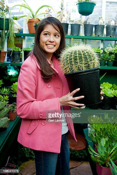 Woman holding cactus plant at nursery