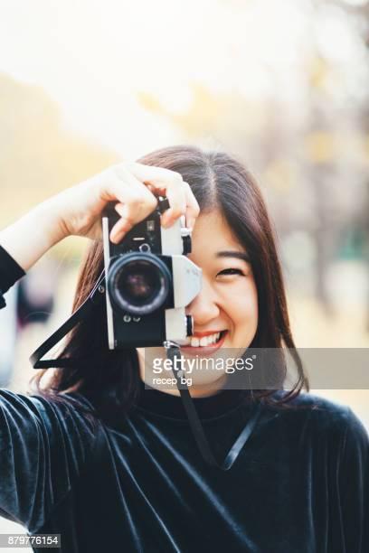 女性保持しているカメラと笑顔