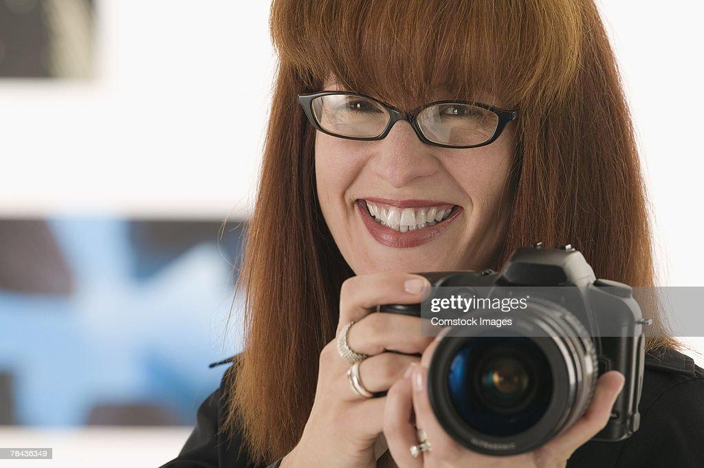 Woman holding camera : Stockfoto