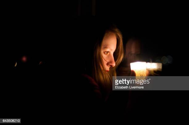 woman holding candle in the dark - candle in the dark imagens e fotografias de stock
