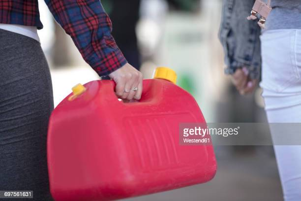 Woman holding canister at fuel station
