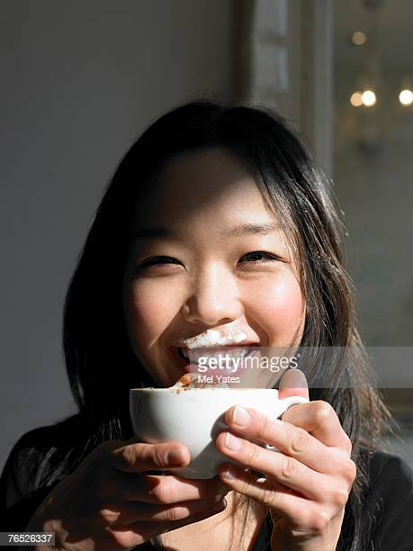 Woman holding cappuccino, with foam on upper lip, smiling