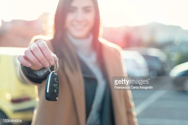woman holding car key - car key stock pictures, royalty-free photos & images