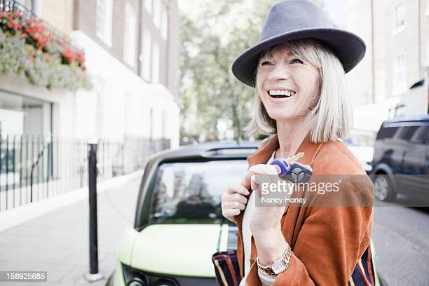 woman holding car keys on city street - nancy green stock pictures, royalty-free photos & images