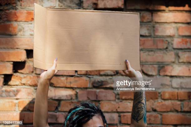 woman holding cardboard in hands, fight for gender equality, feminism, girl power - international womens day stock pictures, royalty-free photos & images