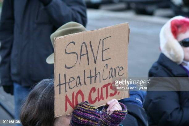 woman holding cardboard with text - protest olympia stock pictures, royalty-free photos & images