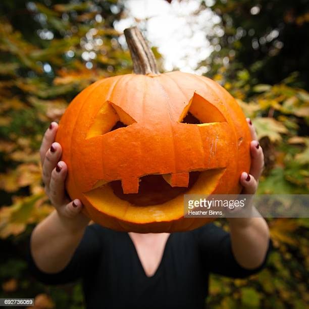 woman holding carved pumpkin - scary pumpkin faces stock photos and pictures