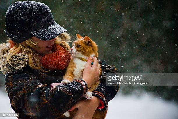 Woman holding cat in arms during snow