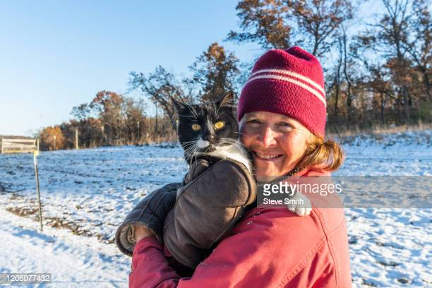 woman holding cat in snow - cat with red hat stock pictures, royalty-free photos & images