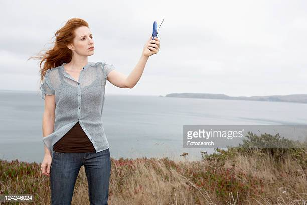 Woman holding cell phone at beach
