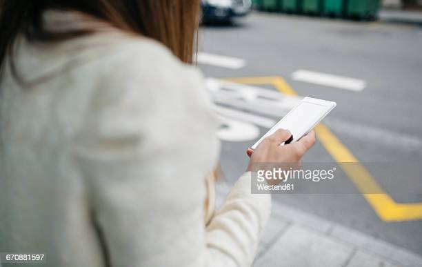 Woman holding cell phone at the roadside