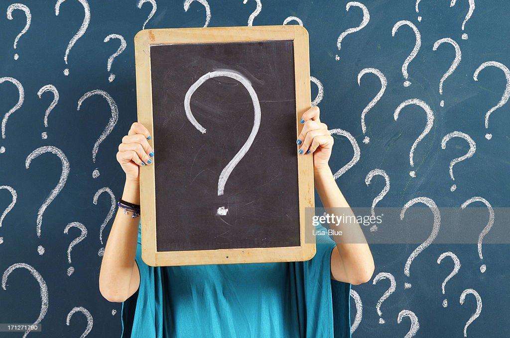 Mujer agarrando chalkboard con signo de interrogación : Foto de stock