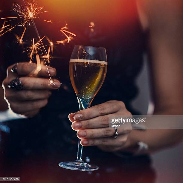 Woman holding champagne and sparkler close-up