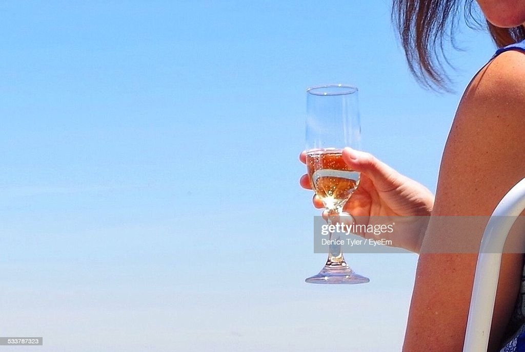 Woman Holding Champagne Flute At Beach : Foto stock
