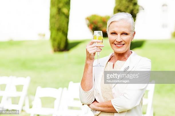Mulher a segurar Flute de Champanhe, ao ar livre em Casamento