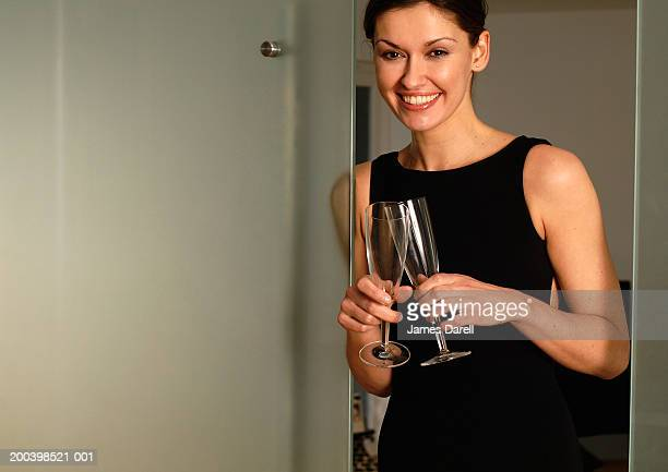 woman holding champagne glasses, smiling, portrait - cocktail dress stock pictures, royalty-free photos & images