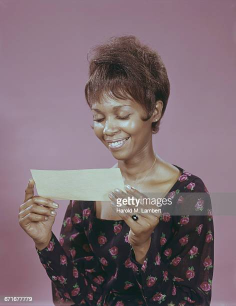 woman holding check and smiling  - {{relatedsearchurl(carousel.phrase)}} ストックフォトと画像