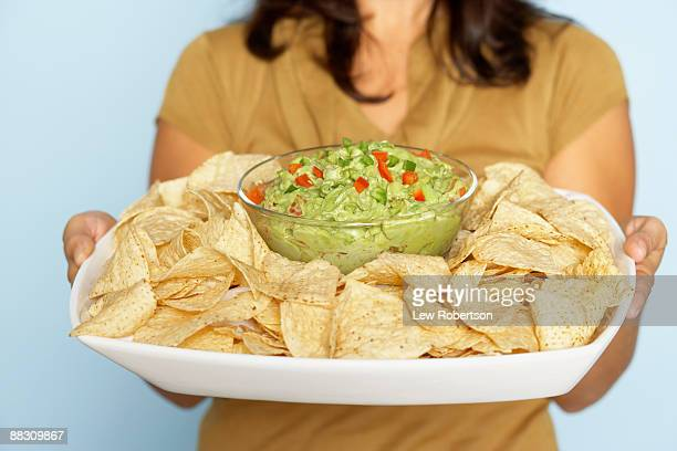 Woman holding chips and guacamole