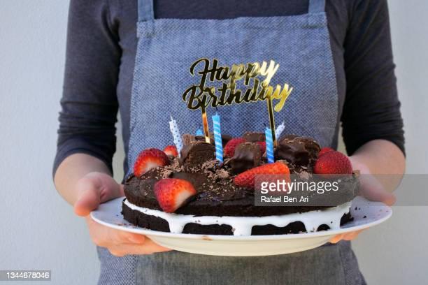 woman holding chocolate birthday cake decorated with happy birthday sign - rafael ben ari imagens e fotografias de stock