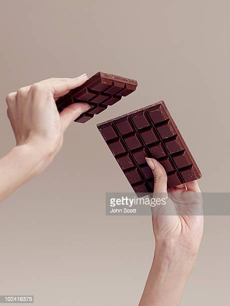woman holding chocolate, close-up of hands - chocolate bar stock pictures, royalty-free photos & images