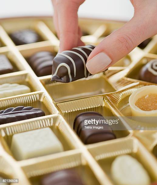 Woman holding chocolate over box of chocolates
