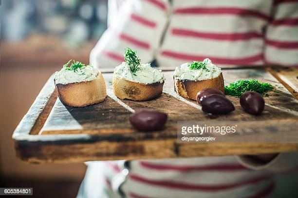 Woman holding chopping board with Bruschetta with soft cream cheese and olives