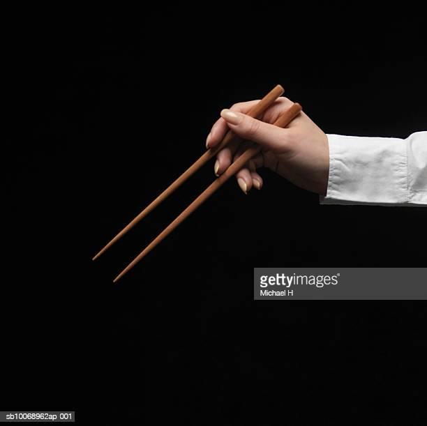 Woman holding chopsticks, close-up