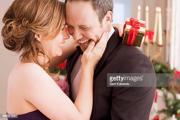 Woman holding Christmas gift and hugging man