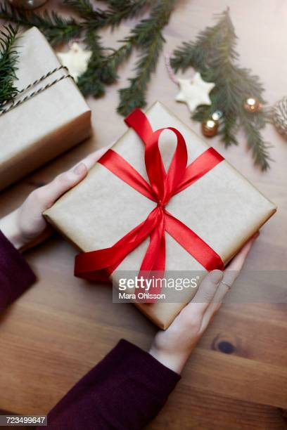 Woman holding Christmas gift tied with red bow, close-up