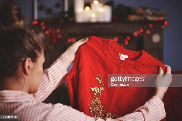woman holding christmas jumper - christmas jumper fotografías e imágenes de stock