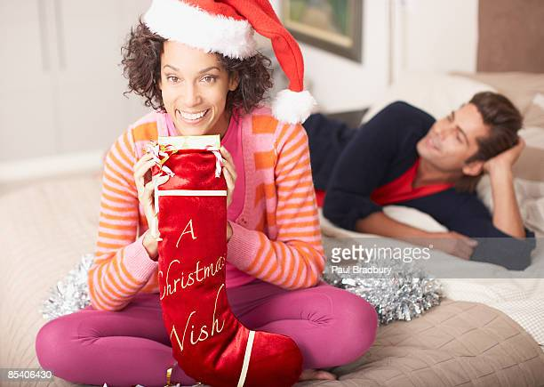 woman holding christmas stocking - christmas stocking stock pictures, royalty-free photos & images