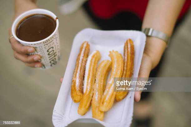 woman holding churros - churro stock photos and pictures