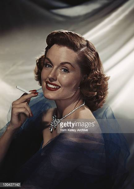 woman holding cigarette, smiling, portrait - smoking issues stock pictures, royalty-free photos & images