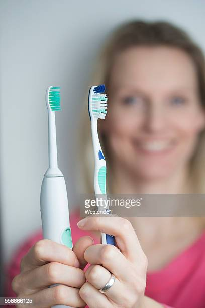 Woman holding classical and electric toothbrush