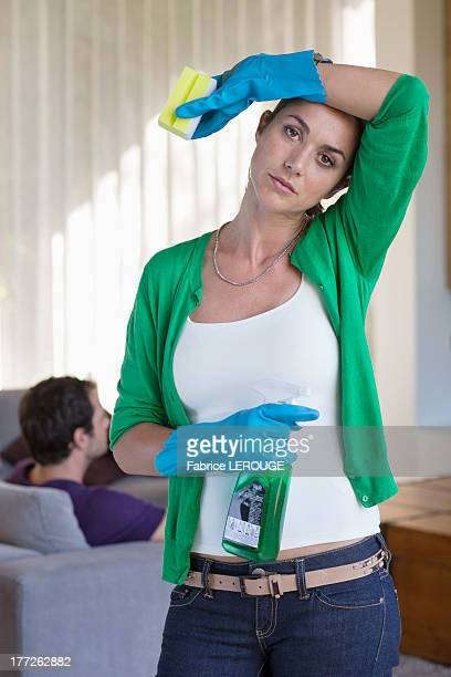 Woman holding cleaning equipment and looking tired with her husband sitting on a couch