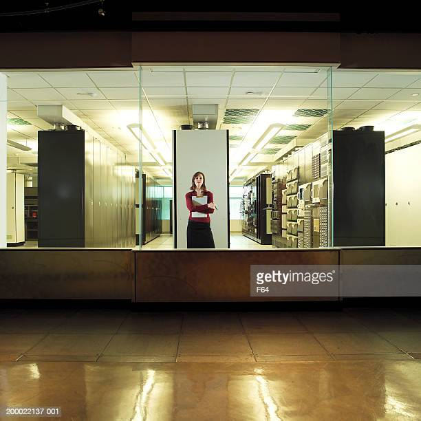 Woman holding clipboard in computer server room